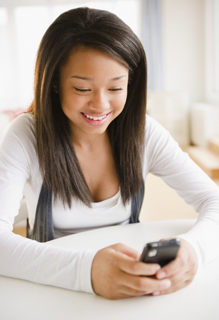 Smiling mixed race teenage girl text messaging on cell phone
