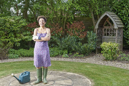 Mixed race woman with watering can in backyard LANG_EVOIMAGES