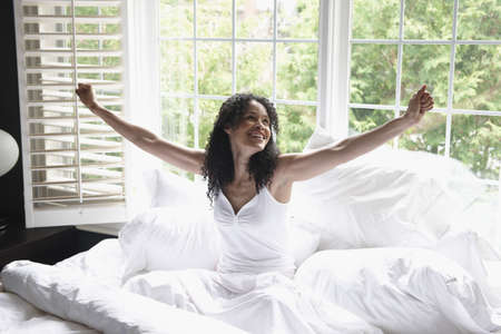 Black woman waking up in bed LANG_EVOIMAGES