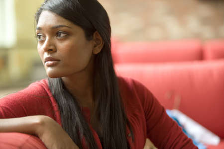 Concerned mixed race woman sitting on sofa