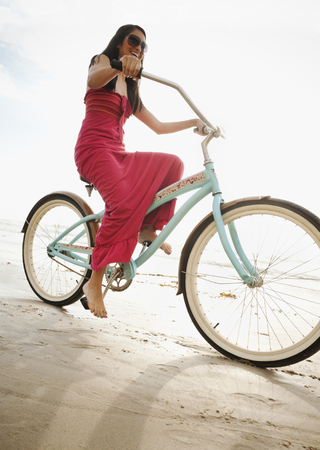 Hispanic woman riding retro bicycle on beach LANG_EVOIMAGES
