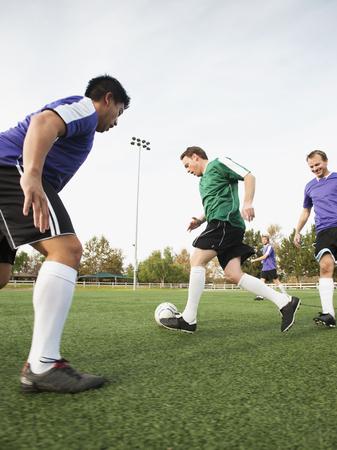 Men playing soccer on soccer field LANG_EVOIMAGES