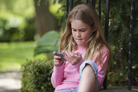 Caucasian girl text messaging with cell phone on front stoop