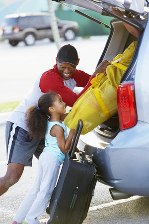 African American father and daughter loading car