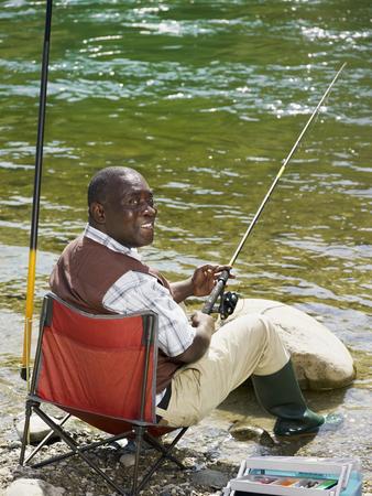 Smiling Black man fishing in stream