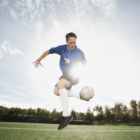 Caucasian soccer player kicking soccer ball