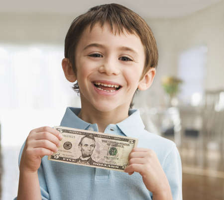 Grinning Caucasian boy holding five dollar bill LANG_EVOIMAGES
