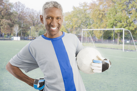 Mixed race man in soccer uniform holding ball