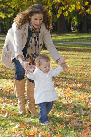 Mother helping daughter walk in park LANG_EVOIMAGES