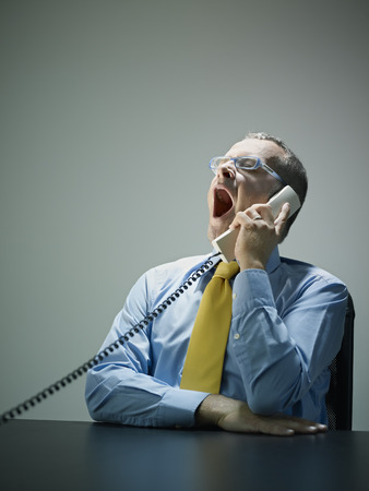 Caucasian businessman yawning and talking on telephone LANG_EVOIMAGES