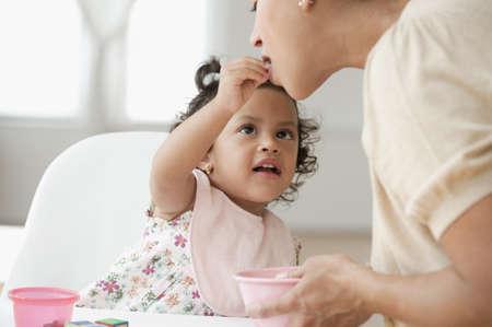 Hispanic girl feeding mother