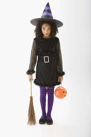 Mixed race girl in Halloween costume holding broom and jack olantern