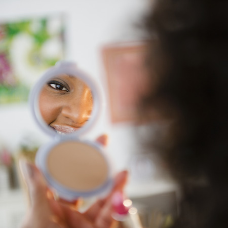 African American woman looking at reflection in compact