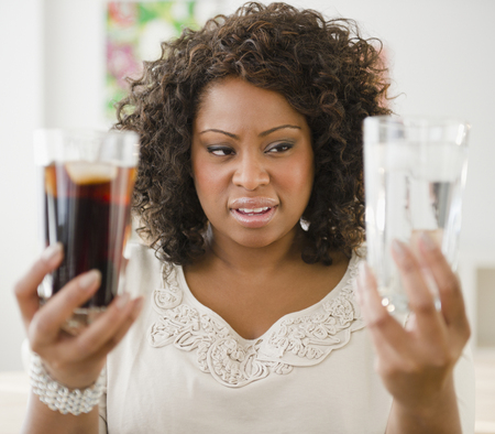 African American woman looking at water and soda
