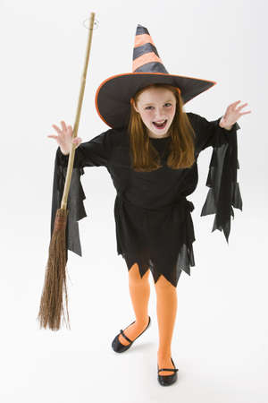 Caucasian girl in witch costume holding broom LANG_EVOIMAGES