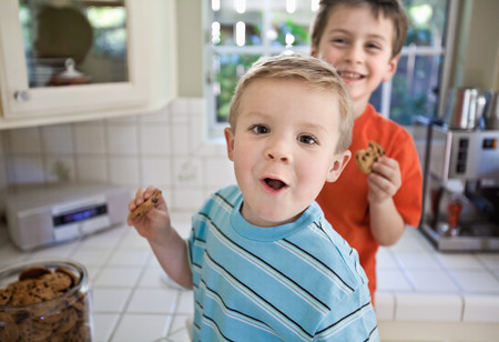 Caucasian brothers sneaking cookies in kitchen