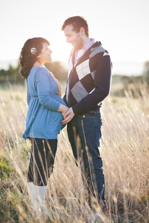 Pregnant woman holding husbands hands in field