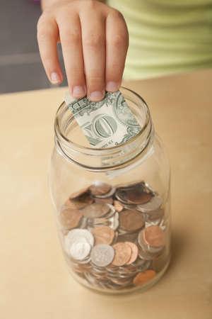 African American girl putting money into jar