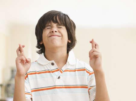 Caucasian boy crossing fingers LANG_EVOIMAGES