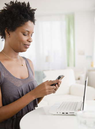Black woman text messaging on cell phone LANG_EVOIMAGES