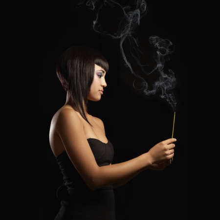 Mixed race woman holding burning incense stick