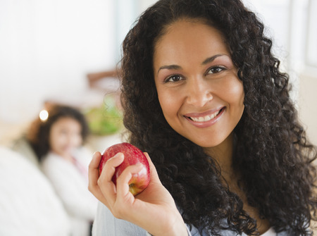 Mixed race woman holding red apple LANG_EVOIMAGES