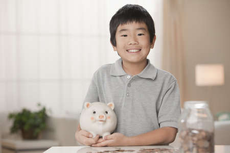 Korean boy putting coins in piggy bank LANG_EVOIMAGES