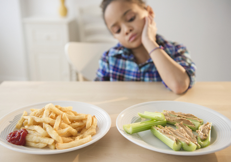 African American girl looking at healthy and unhealthy food LANG_EVOIMAGES