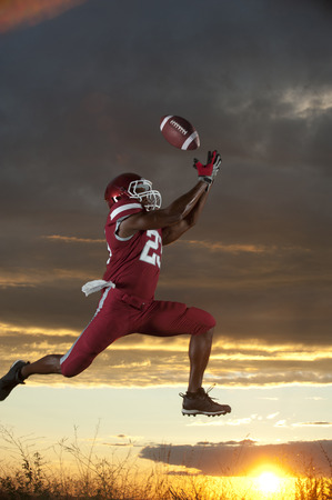 Black football player catching football player in mid-air LANG_EVOIMAGES