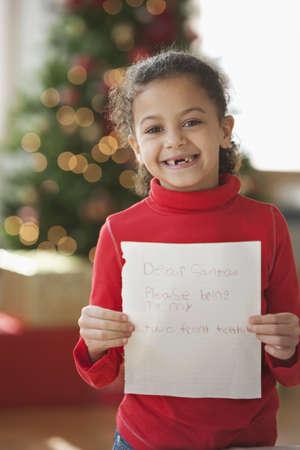 Hispanic girl writing Christmas letter to Santa LANG_EVOIMAGES
