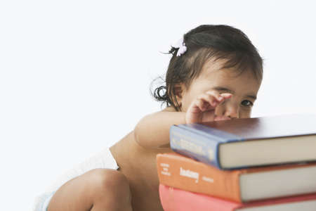 Hispanic baby girl reaching for book LANG_EVOIMAGES