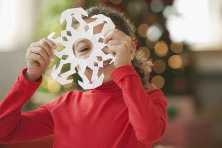 Hispanic girl making Christmas paper snowflake LANG_EVOIMAGES