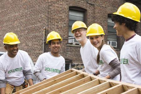 Volunteers lifting construction frame together LANG_EVOIMAGES