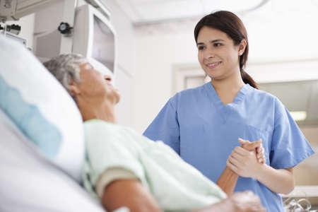 Nurse comforting patient in hospital bed LANG_EVOIMAGES