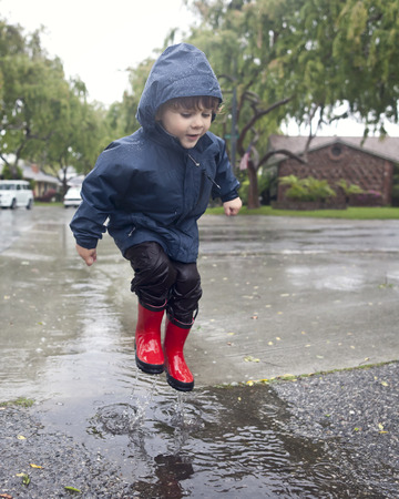 Caucasian boy jumping in rain puddle LANG_EVOIMAGES