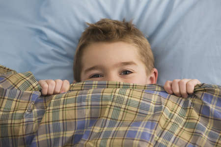 Caucasian boy laying in bed covering his face with blanket