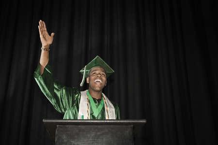 Mixed race high school graduate speaking at podium