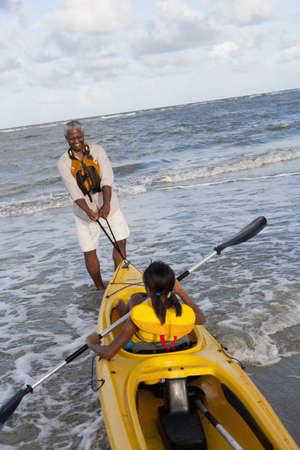 Black grandfather going kayaking with granddaughter