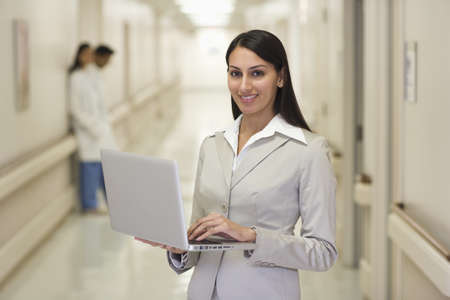 Indian businesswoman standing in hospital corridor holding laptop