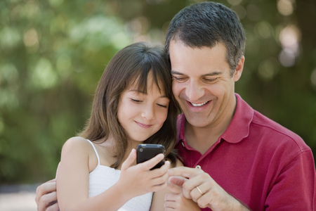 Hispanic father and daughter text messaging on cell phone