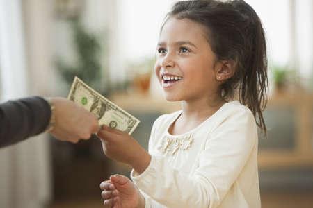 Mother handing girl one dollar bill LANG_EVOIMAGES