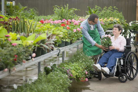 Florist helping customer seated in wheelchair LANG_EVOIMAGES