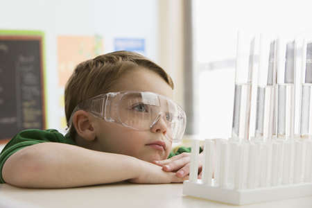 Caucasian boy looking at liquid in test tubes