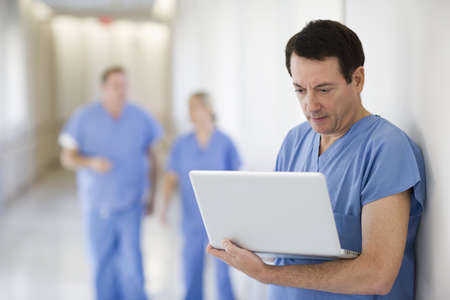 Doctor using laptop in hospital corridor