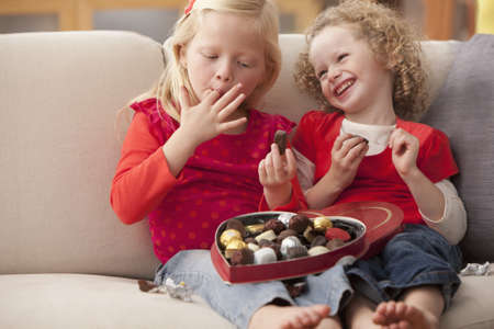 Caucasian girls eating Valentines candy LANG_EVOIMAGES