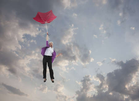 Caucasian businesswoman holding umbrella and falling through clouds LANG_EVOIMAGES