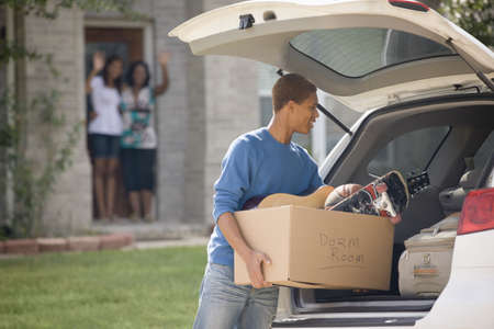 Mixed race teenager loading car for college LANG_EVOIMAGES