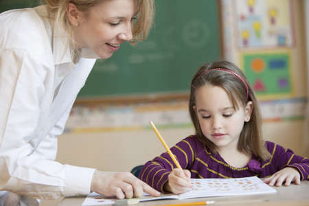 Teacher helping Caucasian girl studying in classroom LANG_EVOIMAGES