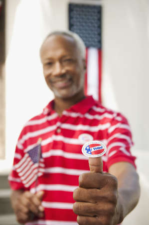 African American man holding an I Voted sticker LANG_EVOIMAGES