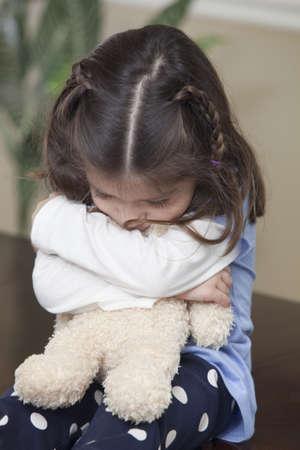 Young girl hugging teddy bear